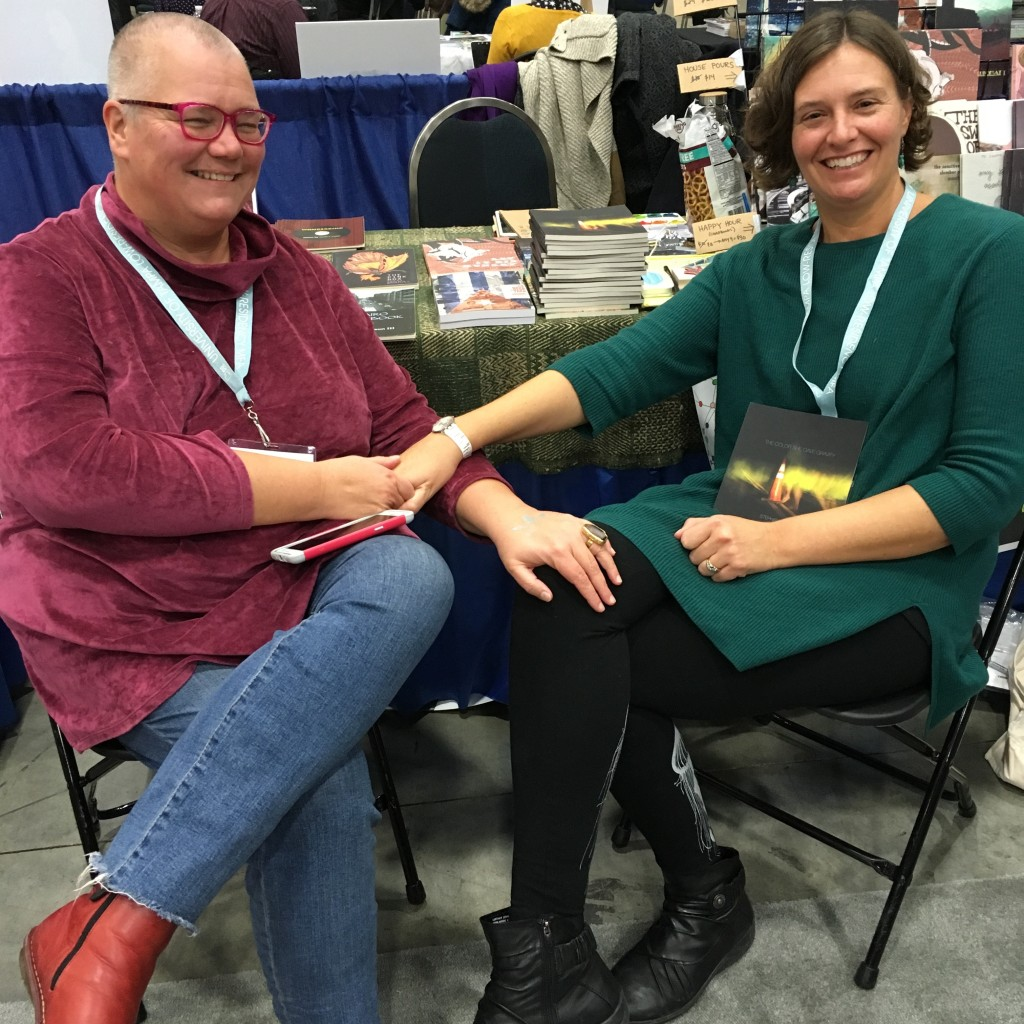 Heit (r) with her partner, the poet, performance artist, and disability activist Petra Kuppers (l), at the OS table at AWP 17.